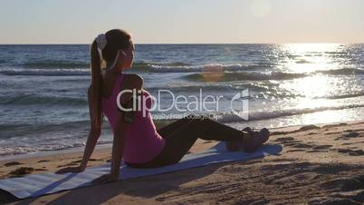 Fitness sporty woman relaxing after workout while listening music on beach at sunset