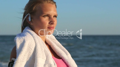 Face of fitness girl relax listening to music after workout on the beach