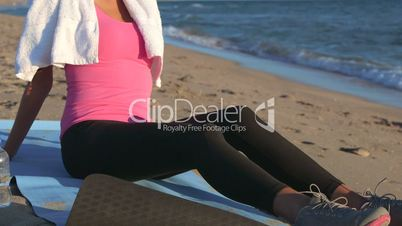 Fitness girl relaxing after workout on the beach