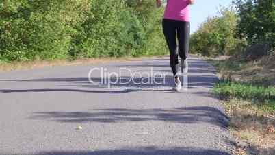 Fitness female runner jogging along road at summer