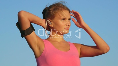 Fitness woman on workout with earphones and sport smartphone armband