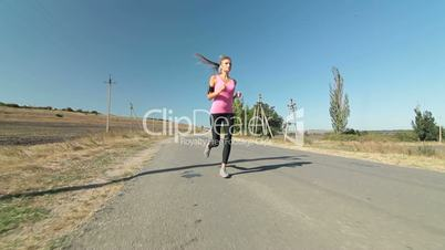 Fitness athletic girl jogging along the road during outdoor workout