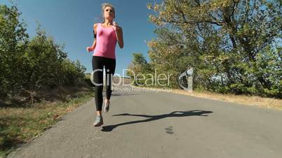 Fitness routine for women - athletic girl runner jogging along road