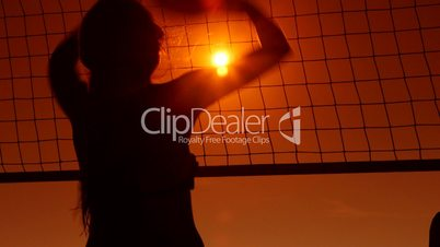 People enjoy playing volleyball on beach at sunset