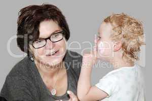Woman putting cream on a playful child