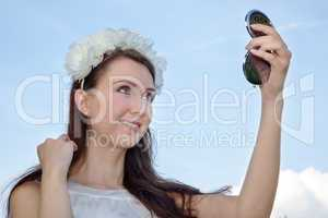 Woman looks at herself in the compact mirror
