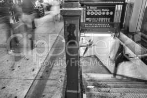New York City. Subway entrance and stairs at night with moving p