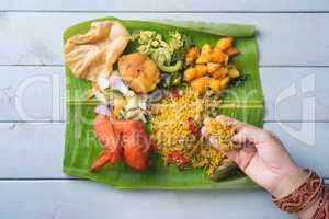 Indian woman eating biryani banana leaf rice