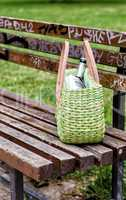 Green straw bag on a park bench