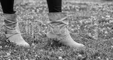 Woman boots on a green garden