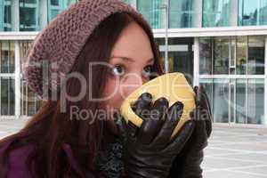 Junge Frau trinken eine Tasse Tee draußen in der Stadt im Winte
