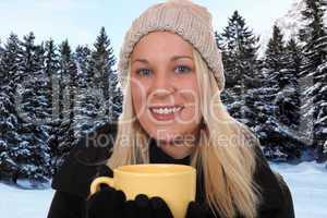 Junge blonde Frau draußen beim Trinken einer Tasse Tee im Winte