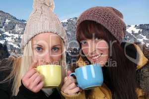 Junge Frauen beim Trinken einer Tasse Tee draußen in den Bergen