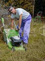 Man mowing overgrown lawn in his yard