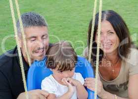 Baby girl on the swing with her parents smiling