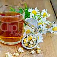 Herbal chamomile tea in mug with strainer on board