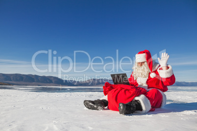 Santa Claus sitting on snow, looking at laptop news