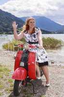 Junge kurvige Frau sitzt auf einem Motorroller mit einem Petticoat-Kleid und winkt