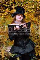 Cosplayer with a book in the autumn park