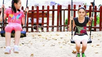 Girls swinging in summer playground