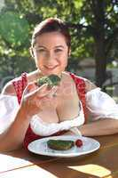 Woman in typical Bavarian costume eats bread with chives in a Ba