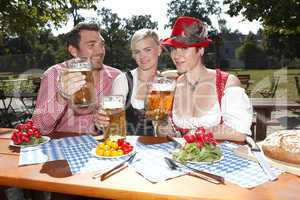 Three Bavarians in traditional costumes sitting in a beer garden