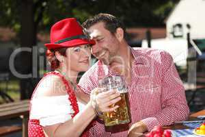 Couple in traditional costumes in a Bavarian beer garden