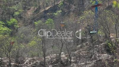 Locked-on shot of overhead cable cars pass above mountain