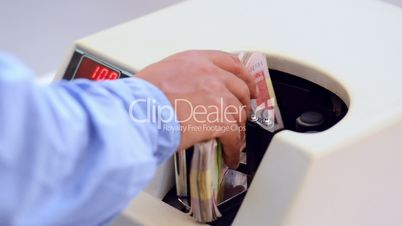 Locked-on shot of Indian currency notes being counted in a machine