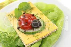 Knäckebrot mit Käse, Basilikum und Marienkäfer