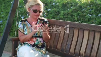 Woman sitting on the garden swing and using smart phone