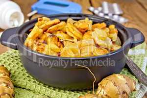 Jerusalem artichokes roasted in pan with meter on board