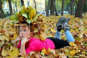 little girl lying on the yellow leaves