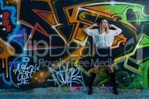Blonde girl in front of graffiti