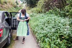 Woman standing next to the car and directed her dirndl dress