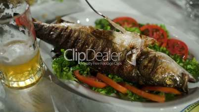 Pouring sauce on fried fish