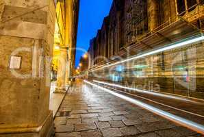 Illuminated street of Bologna at night with bus light trails