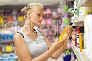 Woman looking at shampoo bottle in the store