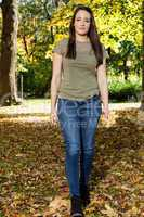 Woman walking in autumnal park and collect leaves