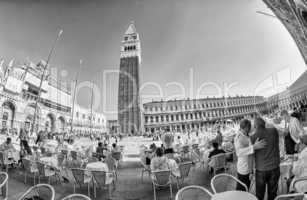 VENICE - APRIL 7, 2014: Tourists enjoy Saint Mark Square on a be