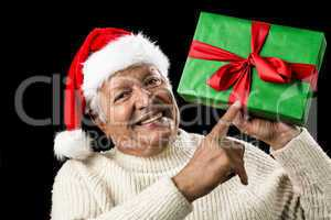 Old Man With Gentle Smile Pointing At Green Gift
