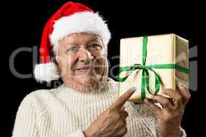 Male Senior With Santa Cap Pointing At Golden Gift