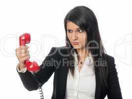 Frau schaut böse auf den Telefonhörer