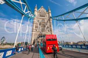 Red bus crossing Tower Bridge on a beautiful summer day - London