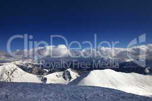 Off-piste slope and beautiful snowy mountains in evening
