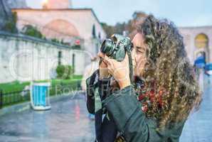 Tourist woman photographing Hagia Sophia at dusk, Istanbul