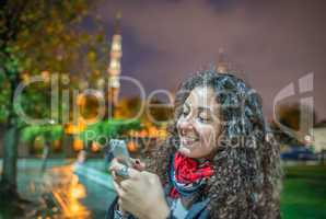 Beautiful tourist female with her smartphone enjoying Blue Mosqu