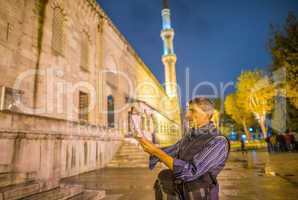 Tourist with map in front of Instanbul Blue Mosque at night