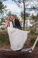 Junges Brautpaar steht frivol auf einer großen Schaukel.