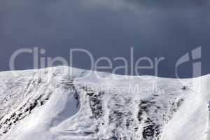 Off-piste slope and storm gray clouds